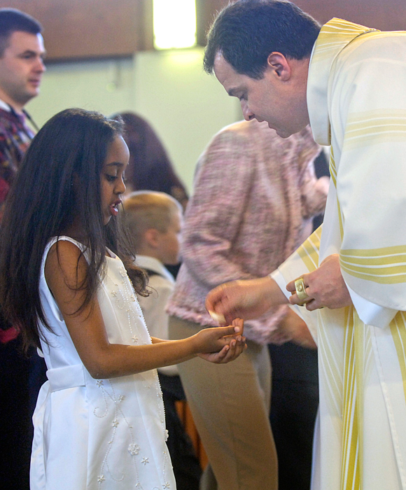 A young girl receiving the Eucharist for the first time